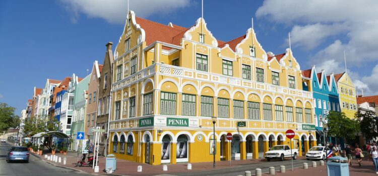 a yellow heritage building in curacao which is stunning to look at with red roof